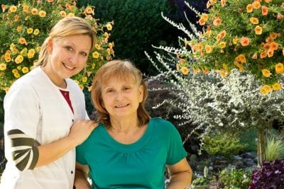 Woman and nurse in an aged care home garden - traits of a good aged care home